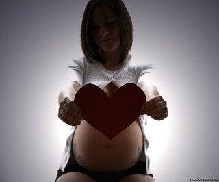 Une femme enceinte avec un cœur en carton