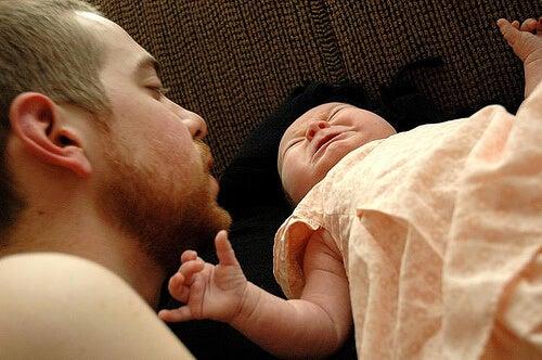 Un papa parle doucement à son bébé, une solution pour calmer les pleurs de votre bébé