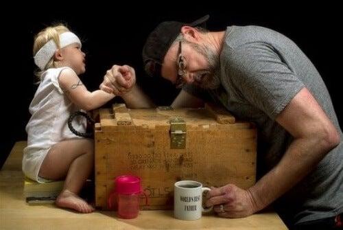 Un papa joue au bras de fer avec sa petite fille