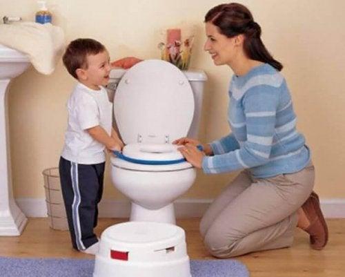 Une maman apprend à son enfant à aller sur le pot