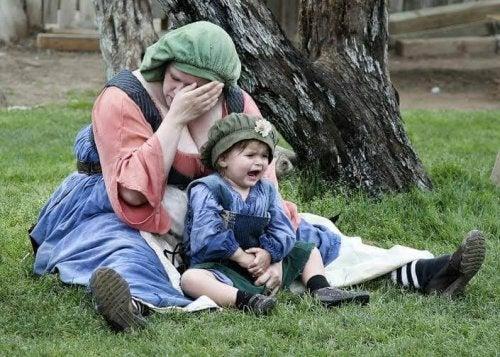 Une maman pleure avec son bébé dans les bras, un symptome du burn-out maternel