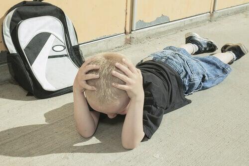 Un petit garçon par terre en train de faire une colère