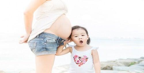 Une petite fille pose sa tête sur le ventre de sa maman enceinte, qui attend un deuxième enfant
