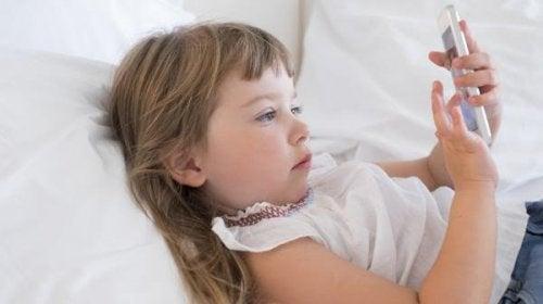 Une petite fille couchée avec un smartphone