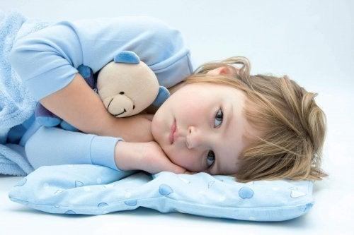 Un petit garçon triste couché avec une peluche
