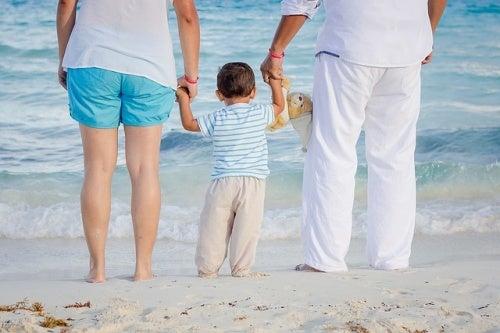 Un petit garçon tient les mains de sa maman et de son papa