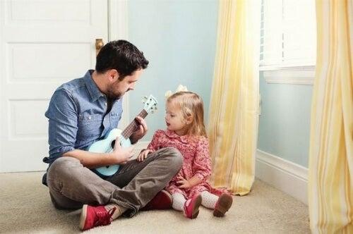 Un papa joue à la guitare avec sa petite fille, ce qui renforce la relation père-fille
