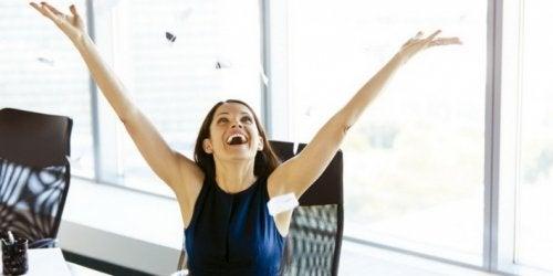 Une femme heureuse les bras en l'air dans son bureau