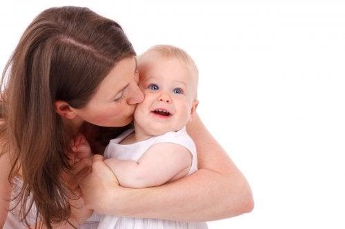 Une maman fait un bisou à sa petite fille, une façon de dire au revoir à votre bébé