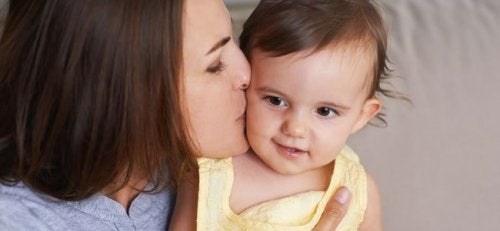 Une maman fait un bisou à son bébé pour lui dire au revoir