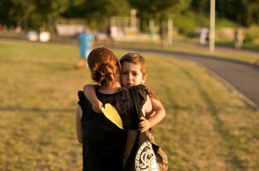 Un enfant triste dans les bras de sa maman