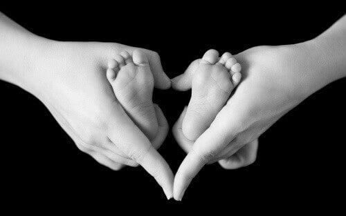 Les pieds d'un bébé dans les mains de sa maman