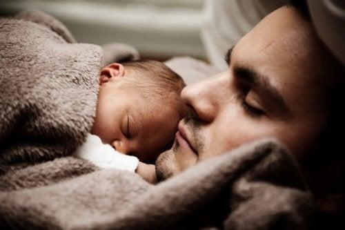 Un bébé endormi sur son papa