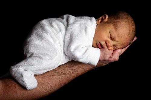 Un bébé endormi sur le bras de son papa