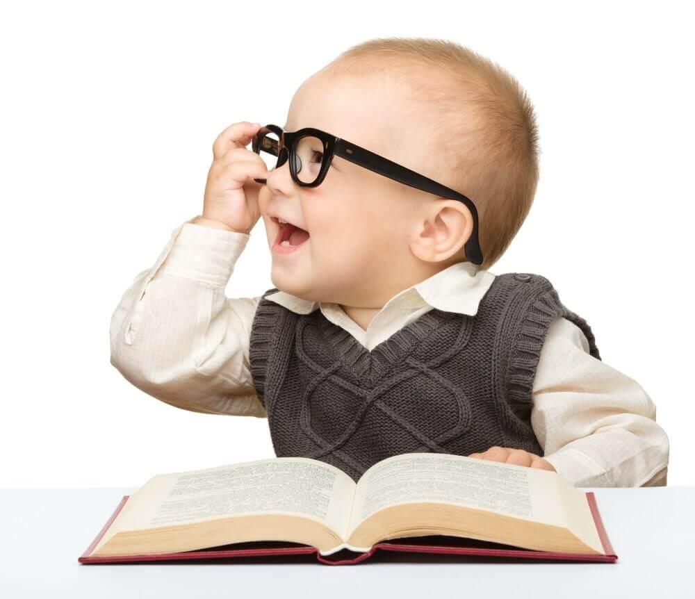 Un bébé avec des lunettes et un livre