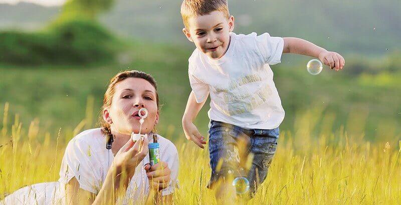 Une tante fait des bulles avec son neveu.