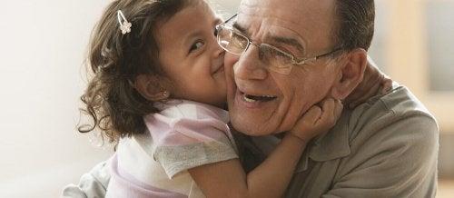 petite fille qui embrasse son grand-père