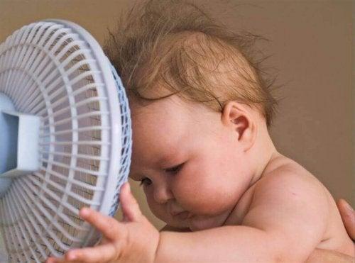 Un bébé devant un ventilateur.