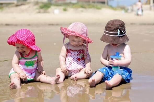 Trois jeunes enfants sur une plage.