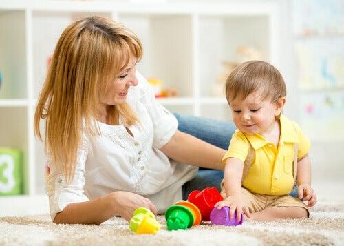 mère jouant avec son enfant assis en tailleur inversé