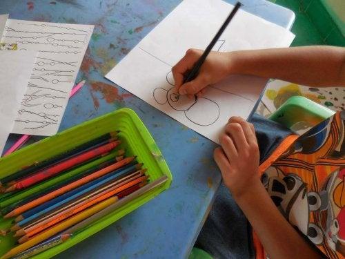 un enfant fait des dessins