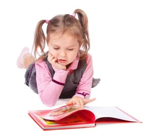 une enfant lit un livre lié à l'année scolaire