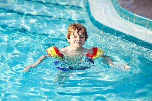 enfant se baigne avec brassards