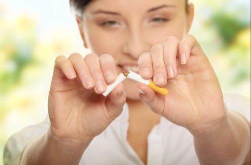 Une femme rompt une cigarette en deux