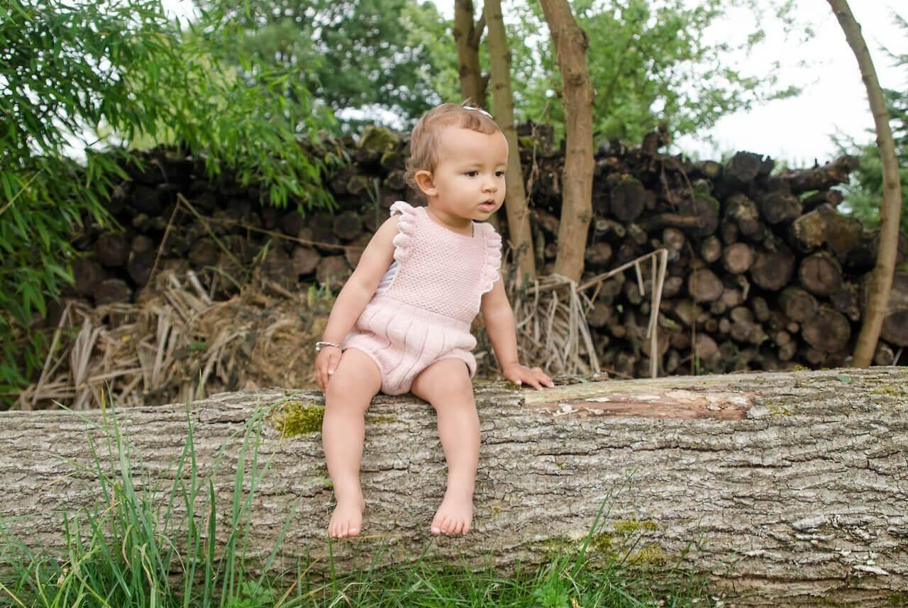 Un bébé est assis sur une branche