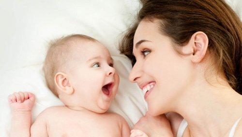 stimuler l'ouïe Une mère sourit à son bébé