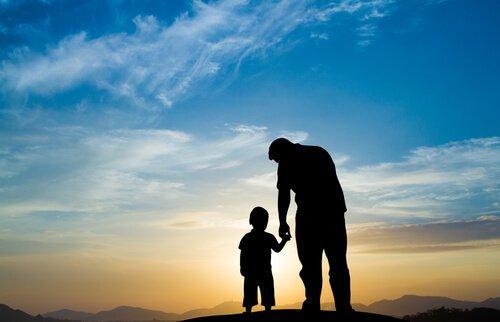 Un père et son fils devant un coucher de soleil