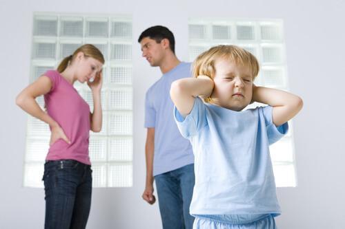Un enfant se bouche les oreilles pour ne pas entendre les disputes de ses parents