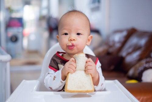 Un bébé mange du pain