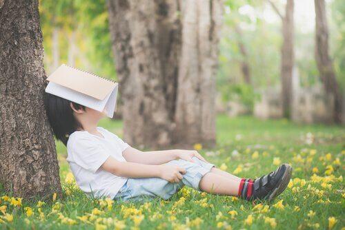 Un enfant se cache la figure avec un livre