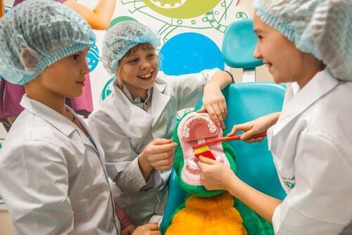Des enfants brossent les dents d'un crocodile comme expérience