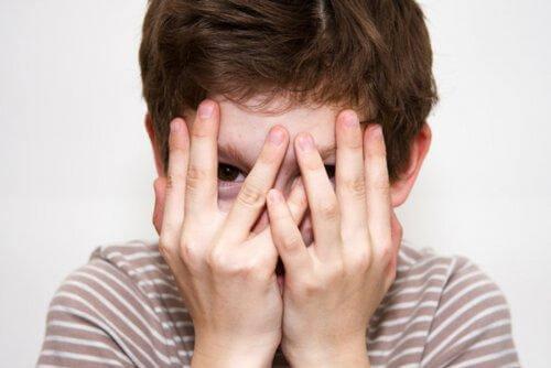 Un enfant timide se cache le visage