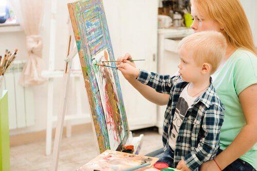 Un enfant en train de peindre avec sa mère