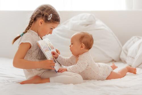 Un bébé écoute sa soeur lui lire une histoire