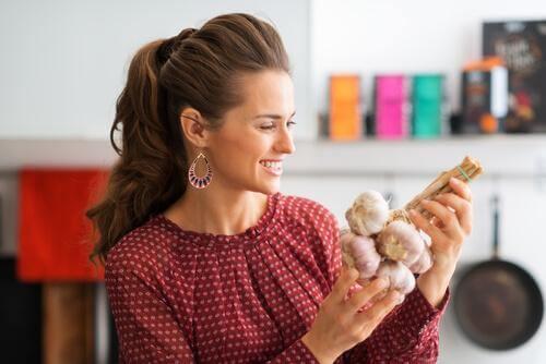 Une femme souriante tient de l'ail