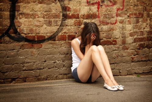 Une adolescente assise en train de pleurer