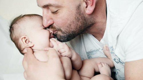 Un père fait un bisou à son bébé