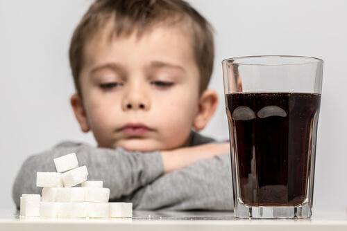 Un enfant devant un verre de soda et son équivalent en sucre