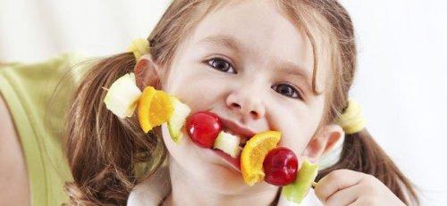 Une fille mange une brochette de fruits