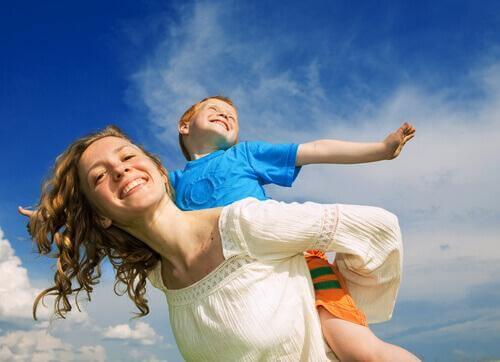 Une mère porte son fils sur ses épaules