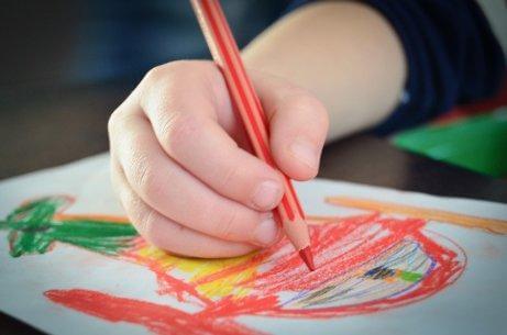 Un enfant dessine au crayon