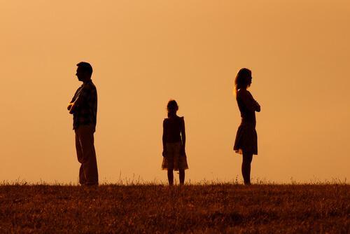 Un enfant entre ses deux parents séparés