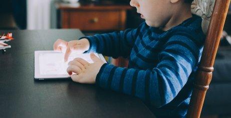 Un enfant joue sur sa tablette