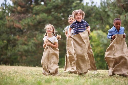 Les enfants font une course en sac
