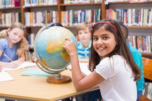 Une élève montre la mappemonde avec son doigt