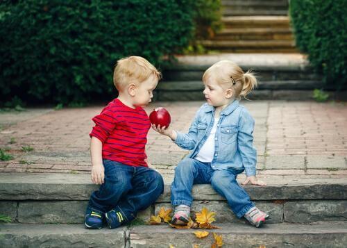 Deux enfants partagent une pomme